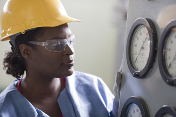 Black worker in hard-hat looking at gauges