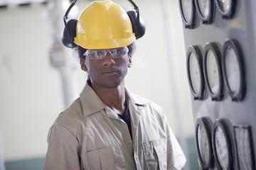 Black worker in control room wearing hard-hat