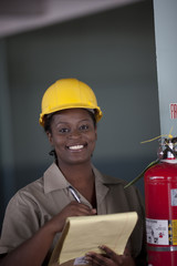 Black worker in hard-hat holding clipboard