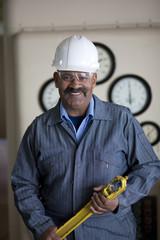 Hispanic worker in hard-hat holding tool