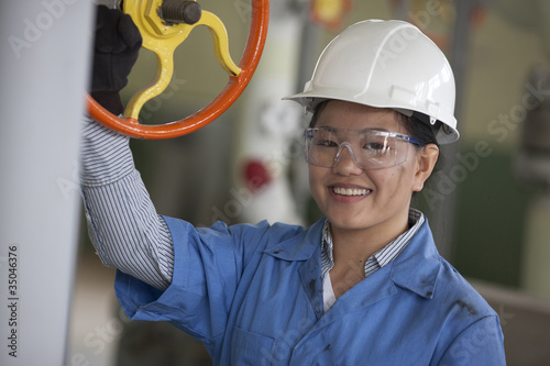 Chinese worker in hard-hat turning valve