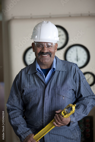 Hispanic worker in hard-hat holding tool