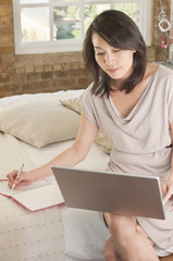 Korean woman sitting on bed using laptop and writing