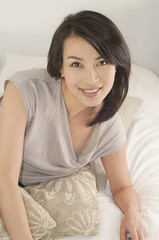 Smiling Korean woman laying in bed