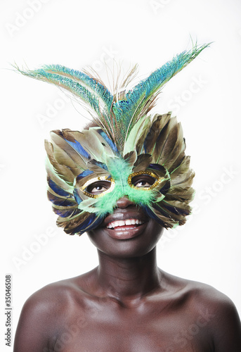 Smiling Black woman in exotic feather mask