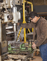 Mixed race machinist working on drill press