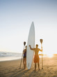 Couple standing on beach with surfboard and paddles