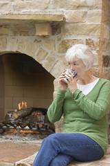 Mixed race woman drinking coffee near fireplace