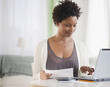 Black woman paying bills on computer