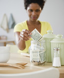 Black woman putting money in jar