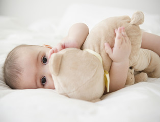 Mixed race baby laying on bed with teddy bear