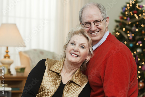 Caucasian couple in living room at Christmastime