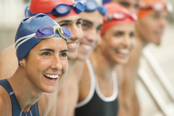 Smiling Hispanic swimmers standing in a row