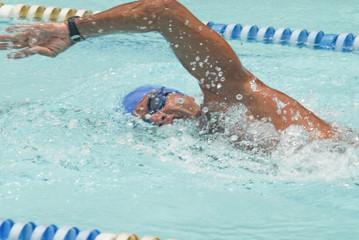 Hispanic man swimming in swimming pool