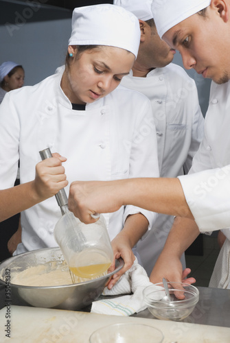 Bakers stirring batter in bakery kitchen