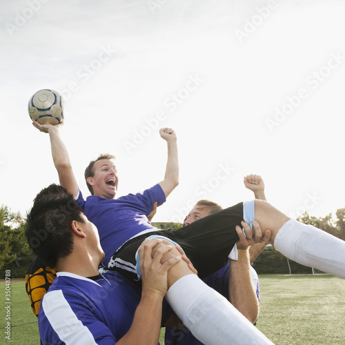 Soccer players lifting teammate and cheering