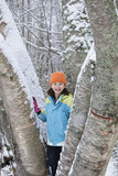 Mixed race girl standing on snowy tree