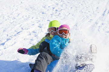 Mixed race girls sledding in snow