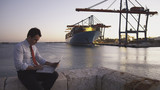 Hispanic businessman with laptop with container ship in background