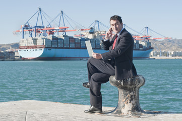 Hispanic businessman holding laptop with container ship in background