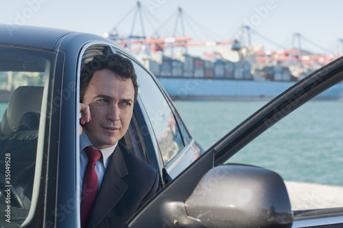 Hispanic businessman using cell phone in car with container ship in background