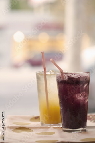 Orange and grape juice in glasses with straws