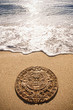 Aztec calendar stone carving on sandy beach