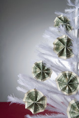 """Cash ornaments on white, artificial Christmas tree"""