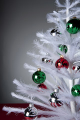 """Ornaments on white, artificial Christmas tree"""