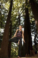 Caucasian woman practicing yoga in forest