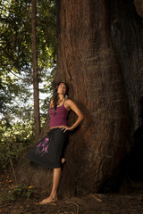 Barefoot Caucasian woman leaning against tree trunk