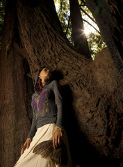 Woman standing on roots of large tree holding feathers