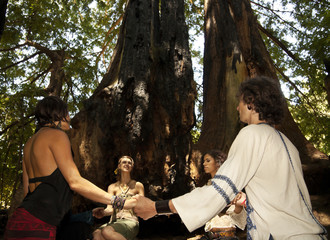 People holding hands in circle in forest