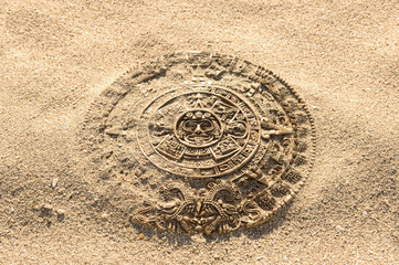 Aztec calendar stone carving on sand