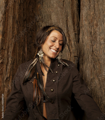 Caucasian woman with feather hair decorations near tree trunk