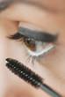 Caucasian woman putting on mascara