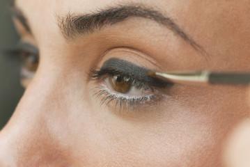 Caucasian woman putting on eyeliner