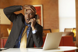 Surprised African American businessman talking on telephone