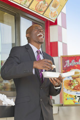 Laughing African American businessman eating lunch