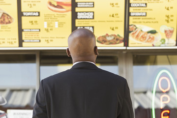 African American businessman looking at cafe menu