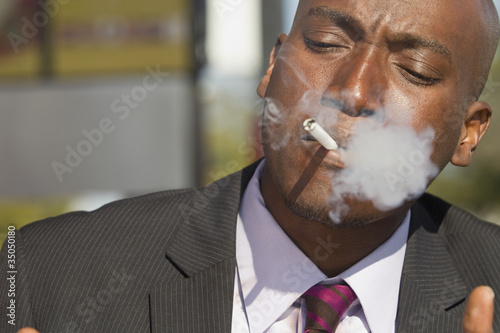 African American businessman smoking cigarette