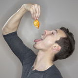 Caucasian man eating a goldfish