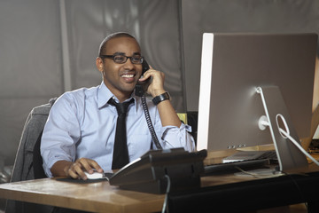 African American businessman working at desk and talking on telephone