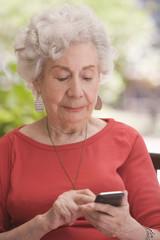 Senior Chilean woman text messaging on cell phone