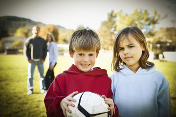 Caucasian boy and girl standing with soccer ball