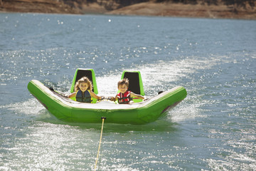 Children riding inflatable raft on lake