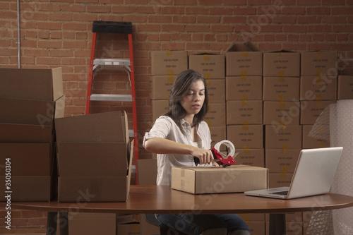 Hispanic woman taping cardboard box