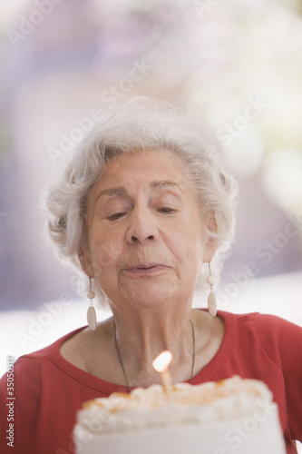 Senior Chilean woman blowing out candle on birthday cake