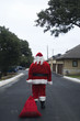 Santa dragging sack down road