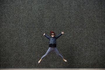 Korean woman jumping on city sidewalk